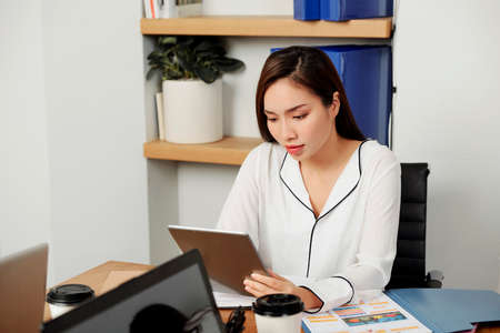 Asian young businesswoman concentrating on her online work she sitting on her workplace and using digital tablet at office Imagens