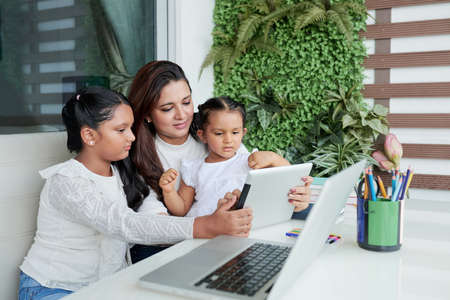 Mother sitting on sofa with her younger and older daughters and they using digital tablet together during their free time at home Stock Photo