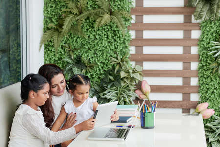 Mother with her two children sitting at the table and watching something together on digital tablet Stock Photo