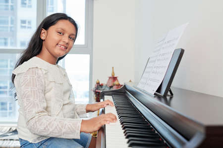 Portrait of student playing the piano and smiling at camera during her lesson at musical school Фото со стока