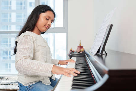 Indian young girl sitting at piano and learning to play on it at musical school Фото со стока