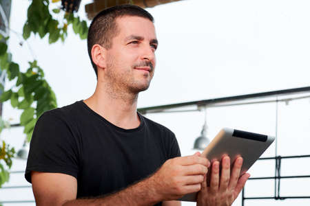 Young handsome man in black shirt holding digital tablet and looking away while sitting at coffee shop