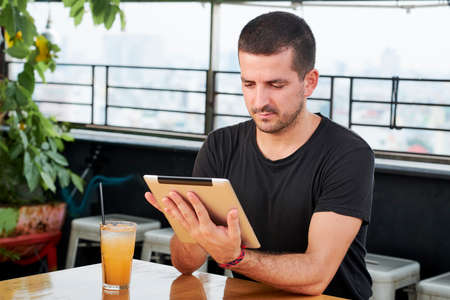 Young man sitting at the table with digital tablet using free wi-fi and drinking juice at outdoor cafe
