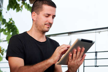 Young man holding digital tablet and touching the display he communicating online while standing outdoors