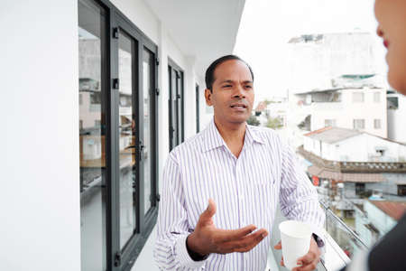 Indian mature businessman standing and talking to his colleague at balcony during coffee break Stock Photo