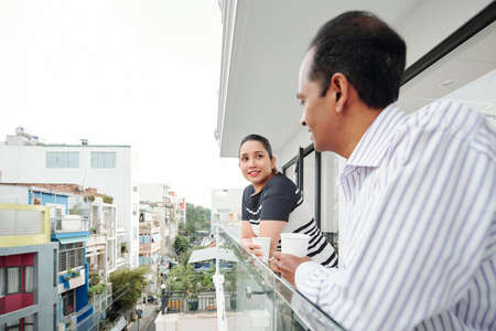 Asian young businesswoman talking to businessman and drinking coffee while they standing at balcony and looking at view of the city