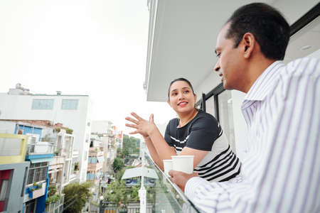 Smiling young businesswoman talking to her partner during their coffee break at balcony