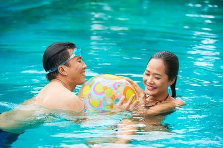 Felice coppia vietnamita che gioca con una palla gonfiabile in piscina