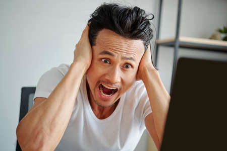 Crazy emotional man covering ears and shouting when reading error mesage on screen of laptop