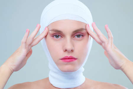 Young woman head bandage listing eyelids with her hands Фото со стока