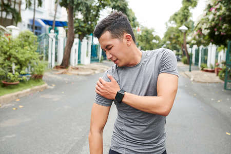 Young Asian man dislocated shoulder when training outdoors Stok Fotoğraf