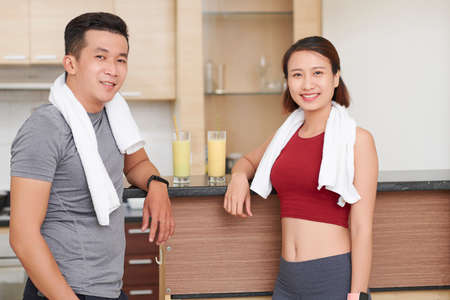 Portrait of happy fitness instructors with towels standing at juice bar in gym