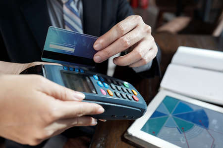 Close-up image of businessman swiping credit card through terminal in hands of waiter to pay for coffee in cafe