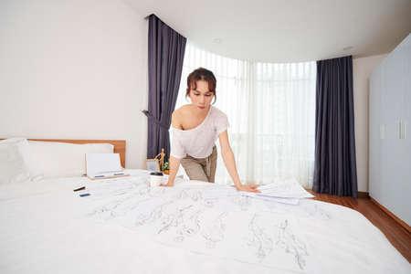 Peinzende jonge modeontwerper die over bed bukt met schetsen van kostuums voor nieuwe voorstelling
