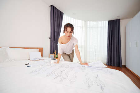 Pensive young transgender fashion designer bending over bed with sketches of costumes for new performance
