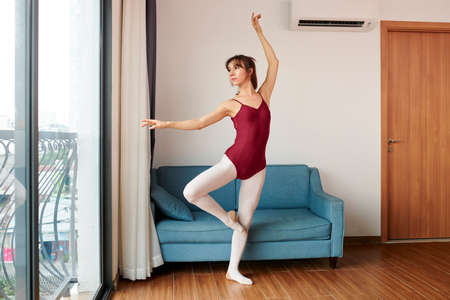 Transgender ballet dancer in tights and leotard practicing new movement for performance