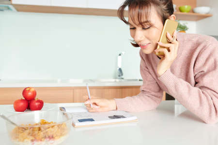 Creative young Asain woman leaning on kitchen table when calling friend and taking notes in journal