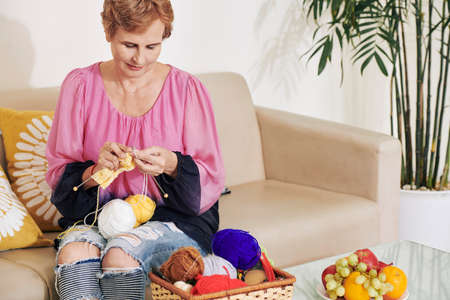 Smiling aged Caucasian woman enjoying knitting new skaft with colorful whool 版權商用圖片