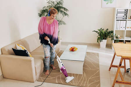 Woman listening to music in headphones when vacuum cleaning carpet in living room Stock Photo