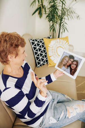 Elderly woman sitting on sofa at home and waving with hand when video calling her family