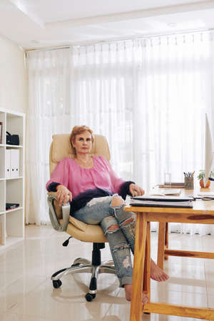 Successful aged businesswoman does not wear shoes when working in her light home office Reklamní fotografie