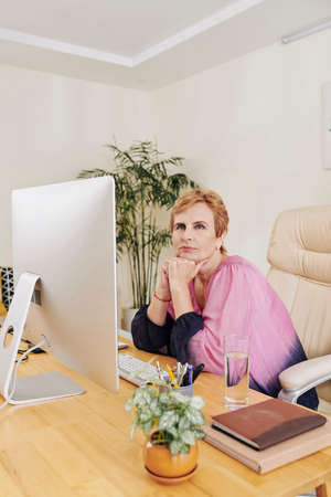 Portrait of pretty aged businesswoman contemplating about future when sitting at her office table