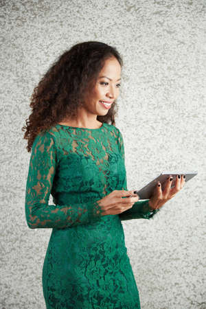 Positive beautiful Asian woman watching video or reading article on tablet computer