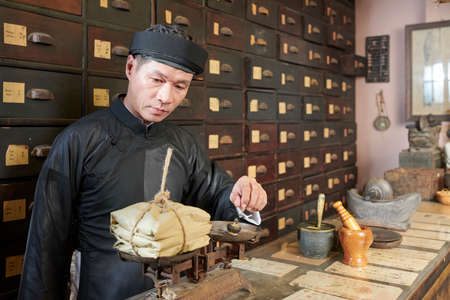 Serious traditional Asian apothecary worker putting plummet on scales to weight package with treatment