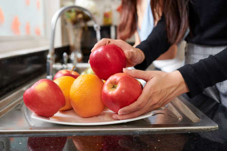 Hands of young woman putting fresh washed fruits on plate 免版税图像