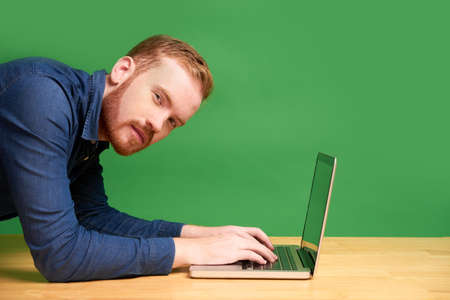 Young man standing in plank position when working on laptop, he is squinting and looking at camera Reklamní fotografie