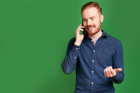 Portrait of cheerful handsome young man gesturing when talking on phone, isolated on green Reklamní fotografie