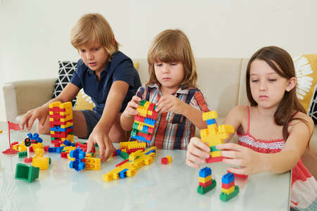 Group of serious children playing with colorful plastic blocks at table at home Imagens