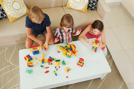 Children sitting on the floor at small table at home and making towers and robots out of plastic blocks, view from above
