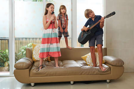 Happy talented kids enjoying playing guitar and singing together at home