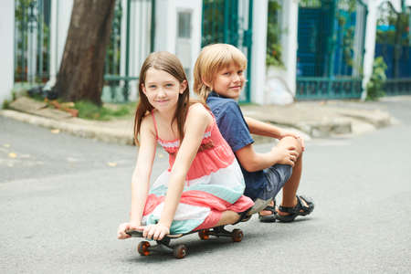 Happy smiling boy and girl riding on skateboard in the street