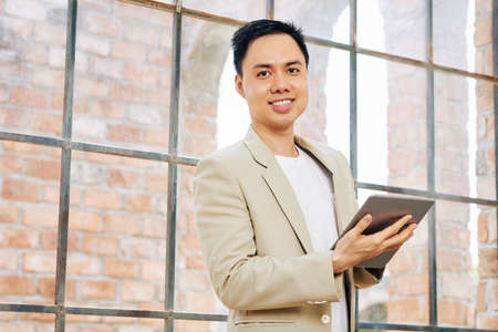 Portrait of positive Asian business executive in light suit working on digital tablet