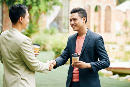 Young Vietnamese businessman with cup of coffee is happy to meet his business partner. They are shaking hands to greet each other
