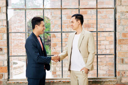 Happy young Asian businessman shaking hand of his smiling coworker in big loft office with brick wall and large windows Фото со стока