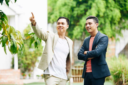 Excited encouraged startupper showing new office building to his young smiling business partner Stock Photo