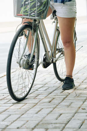 Cropped image of woman sitting on bicycle and resting after long ride in park Stock fotó