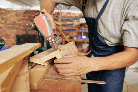 Close-up image of professional carpenter using staple gun when working with wood in his studio