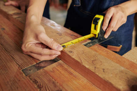 Close-up image of carpenter measuring width of wooden plank