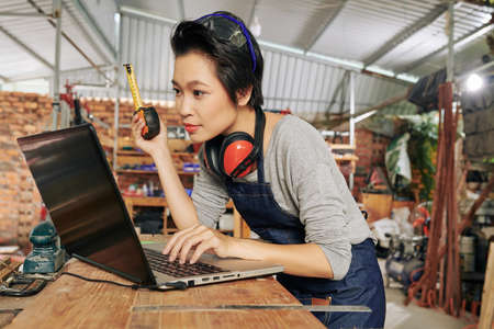 Asian female carpenter with tape measure checking 3D model of furniture piece of tablet computer