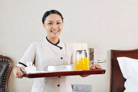 Portrait of Asian waitress standing with tray with food and drinks and smiling at camera she bringing breakfast in the room