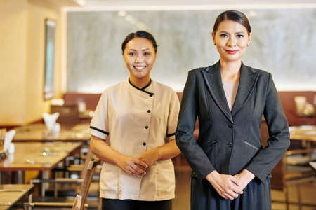 Portrait of Asian manager in suit and waitress in uniform standing together and smiling at camera at restaurant