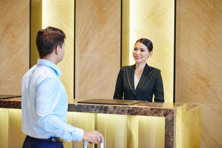 Asian receptionist in black suit smiling and meeting the businessman while standing behind the reception counter at the hotel