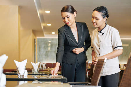 Asian young manager in black suit showing the process of the work in restaurant to the new waitress