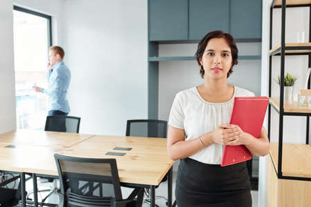 Portrait of young Indian businesswoman standing and holding red folder with businessman talking on the phone in the background at office 版權商用圖片
