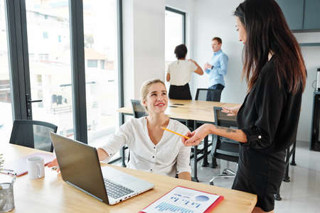 Businesswoman talking to her colleague while she sitting at the table and working with laptop with their partners working in the background at office