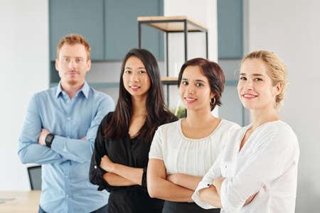 Porträt eines jungen multiethnischen Geschäftsteams, das zusammen mit verschränkten Armen steht und im Büro in die Kamera lächelt